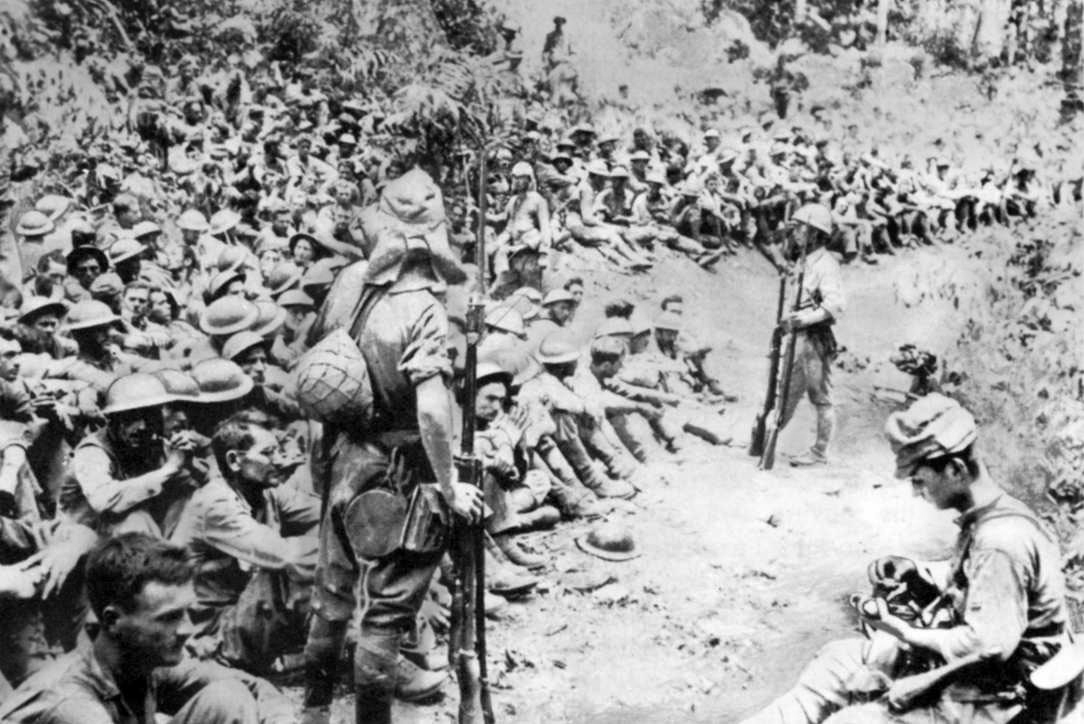 Japanese soldiers standing watch over seated American captives.
