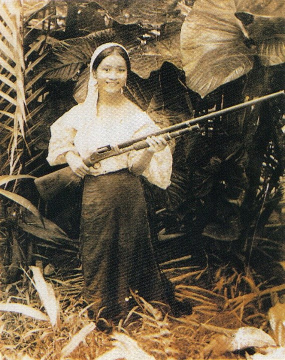 A photograph of a girl from the province of Batangas, a Batangueña, with a smile and a shotgun. Taken in the early 1900s, photographer unknown.