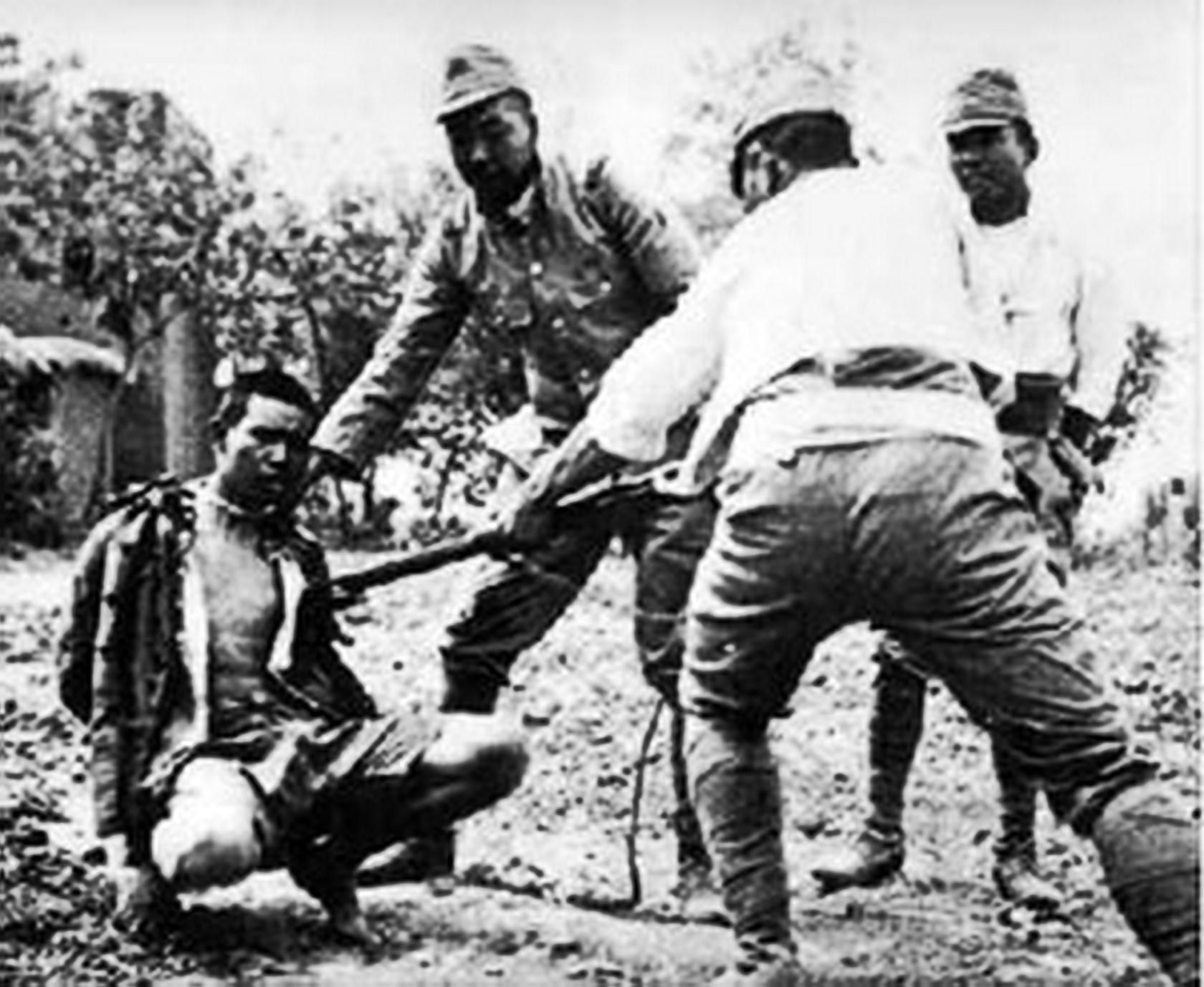 Japanese soldiers harassing a prisoner with a bayonet.