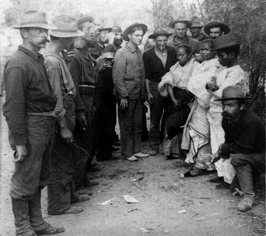 Three Filipinos posed with American soldiers during Philippine-American War.