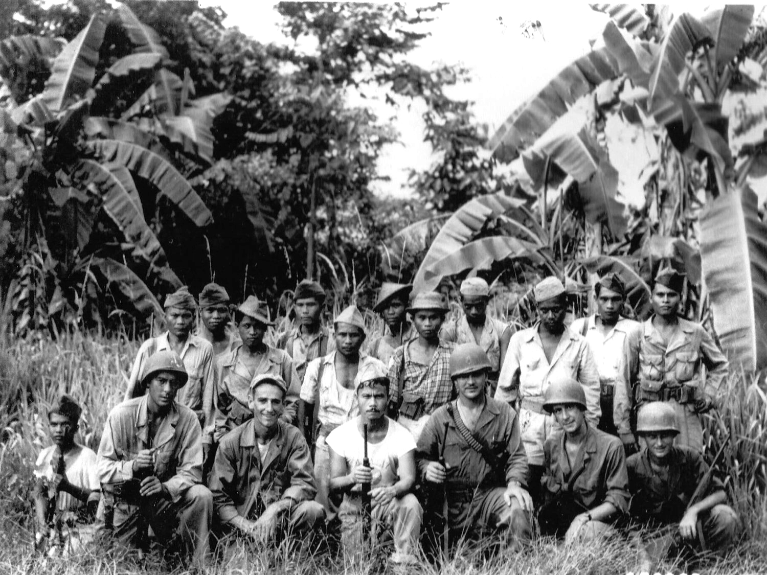Filipino and American troops posing together in the jungle foliage.