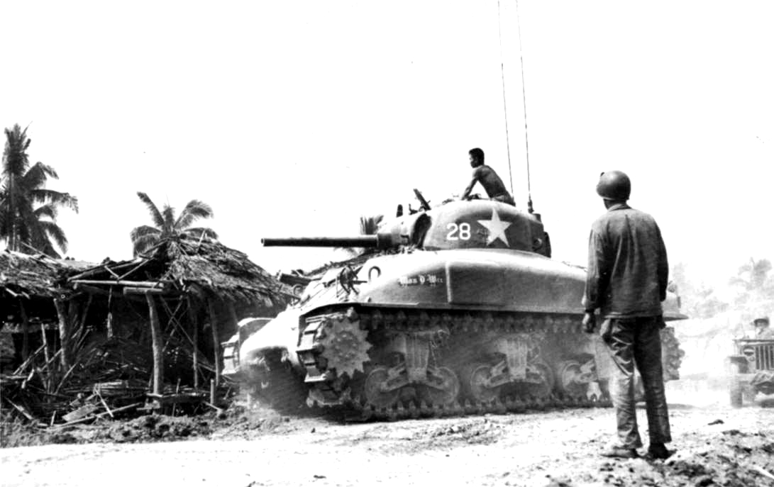 A local villager indicates Japanese positions to an American tank crew in Julita.