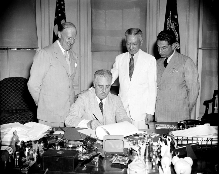 President Franklin Roosevelt signing an economic adjustment of the Philippine Commonwealth on it's way to independence with with Philippine Commonwealth President Sergio Osmeña, U.S. High Commissioner Francis B. Sayre, and Philippine Resident Commissioner Joaquin M. Elizalde.